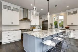 Beautiful kitchen in luxury home interior with island and stainless steel chairs.
