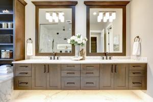 Master bathroom interior in luxury modern home with dark hardwood cabinets.