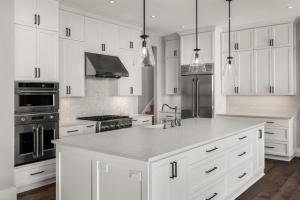 Beautiful kitchen in new luxury home with stainless steel appliances, pendant lights, and hardwood floors.