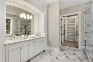 Master bathroom in new luxury home with double vanity and view of walk-in closet